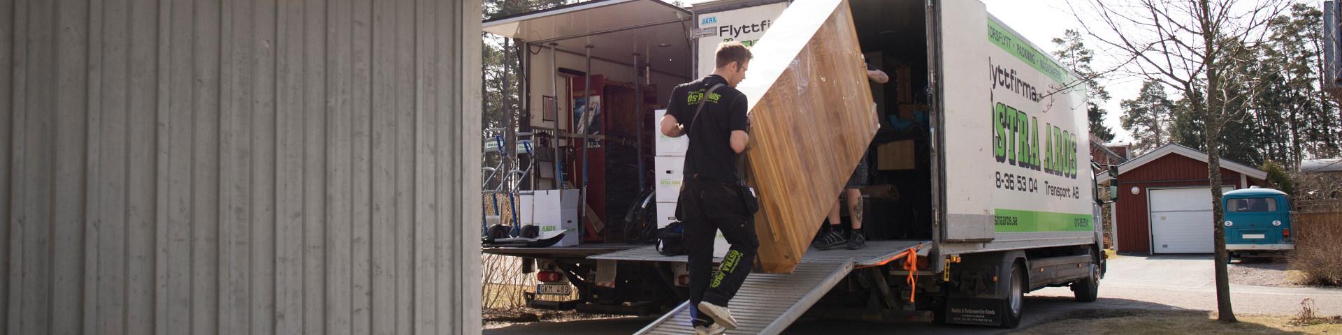 Flyttfirma Östra Aros flyttar ett piano